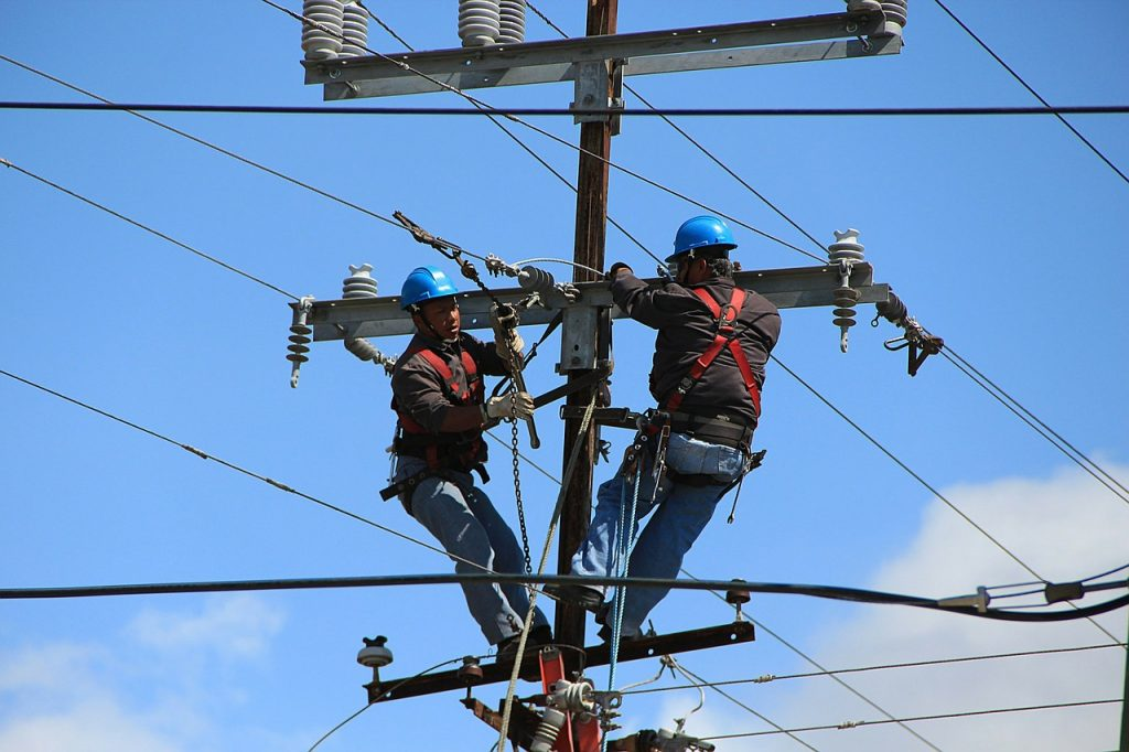 Two Electrical Contractors On An Electrical Pole